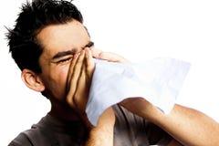Een jonge mens die een koude of een allergie heeft. Stock Foto