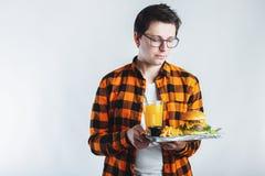 Een jonge mens die in glazen een houten dienblad met een Hamburger, gebraden aardappels en een glas sap houden de student eet sne royalty-vrije stock afbeelding
