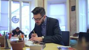 Een jonge mens die, herschrijft een notitieboekje bestuderen stock videobeelden