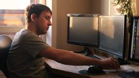 Een jonge mens die klaar voor het werk bij de computer op de zonsondergangachtergrond, neemt een in hand notitieboekje, 4k worden stock videobeelden