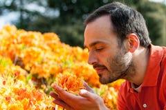 Een jonge mens die van het aroma van de lentebloesem genieten van heldere yello stock afbeelding