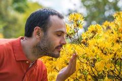 Een jonge mens die van het aroma van de lentebloesem genieten van heldere yello stock fotografie