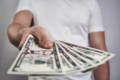 Een jonge mens die een vijf dollarrekening houden, die het geven Royalty-vrije Stock Afbeelding