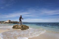 Een jonge mens die zich op een rots bevinden om te vissen royalty-vrije stock fotografie