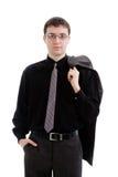 Een jonge mens in een kostuum en band, die een jasje een houden. Royalty-vrije Stock Foto