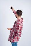 Een jonge mens in een plaidoverhemd maakt selfie Stock Foto