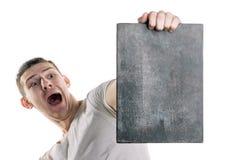Een jonge mens in een T-shirt met een banner voor uw tekst of iets anders, bekijkt de banner met vrees Horizontaal kader stock afbeeldingen