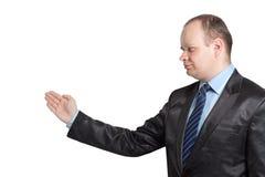 Een mens in een zwart kostuum toont zijn geïsoleerdea hand Stock Foto's