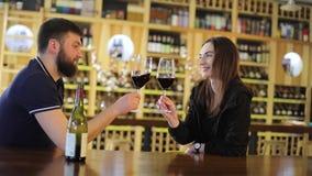 Een jonge mens en een meisje drinken wijn bij een lijst in een restaurant, drinken een man en een vrouw rode wijn in glazen stock videobeelden