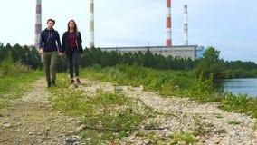 Een jonge mens en een meisje lopen langs de weg langs de rivier stock videobeelden