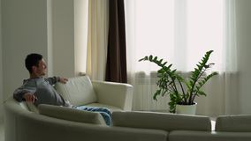 Een jonge mens gaat zitten op de bank en zet verre TV aan stock video
