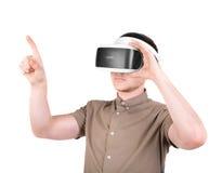 Een jonge mens gebruikt een 3D virtuele die werkelijkheidshoofdtelefoon, op een witte achtergrond wordt geïsoleerd Nieuw en profe Stock Foto