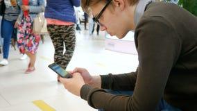 Een jonge mens gebruikt een mobiele telefoon in een winkelcentrum stock videobeelden
