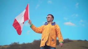Een jonge mens in een geel jasje, jeans en glazen bevindt zich in de bergen en houdt de vlag van Canada stock videobeelden