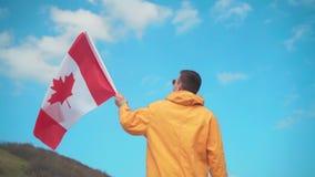 Een jonge mens in een geel jasje, jeans en glazen bevindt zich in de bergen en houdt de vlag van Canada stock video