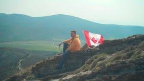 Een jonge mens in een geel jasje, jeans en glazen zit op een rand, die door de vlag van Canada wordt gevolgd stock video