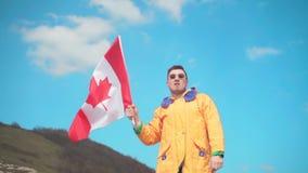 Een jonge mens in een geel jasje, jeans en glazentribunes in de bergen, houdt de vlag van Canada stock videobeelden