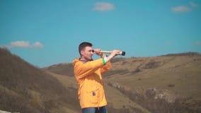 Een jonge mens in een geel jasje, jeans zit op een rots en onderzoekt een kijker De achtergrond is bergen en hemel stock footage