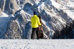 Een jonge mens in een geel jasje loopt op een skihelling met een snowboard stock foto