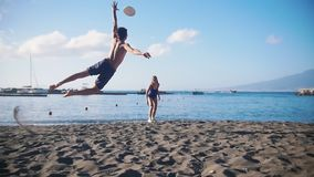 Een jonge mens het spelen frisbee op het strand met zijn meisje Het proberen om de schijf te vangen en het vallen op het zand stock video
