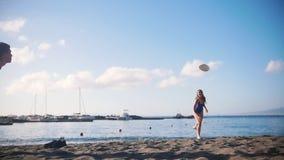 Een jonge mens het spelen frisbee op het strand met zijn meisje Het vangen van de schijf en het vallen op het zand stock video