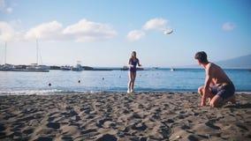 Een jonge mens het spelen frisbee op het strand met zijn meisje Het werpen van de schijf aan haar stock footage