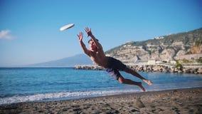 Een jonge mens het spelen frisbee op het strand Sprong en het vangen van de schijf stock footage