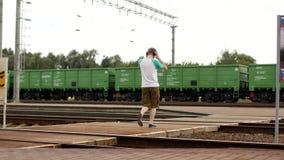 Een jonge mens in hoofdtelefoons kruist de spoorwegsporen en luistert aan muziek, hoort niet de naderbij komende trein stock video