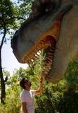 Een jonge mens houdt de dinosaurus achter de tand De dinosaurus heeft een open mondhoogtepunt van scherpe tanden stock fotografie