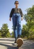 Een jonge mens in jeans en tennisschoenen gaat op de weg onder de bomen stock foto