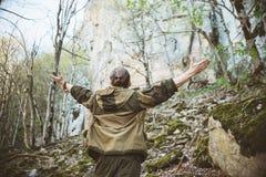Een jonge mens in kampkleren en met een staart op zijn hoofd kijkt en bewondert de grootheid van aard, rotsen en berg Stock Fotografie