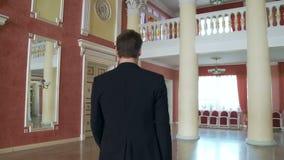 Een jonge mens in een kostuum, loopt de grote zaal met een zekere gang, de mening van de rug stock videobeelden