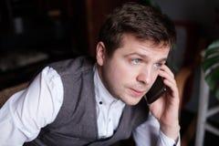 Een jonge mens luistert aandachtig aan wat zij op de telefoon zeggen H stock afbeeldingen