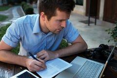 Een jonge mens maakt een businessplan voor zijn persoonlijke zaken royalty-vrije stock afbeelding