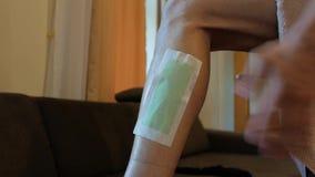 Een jonge mens maakt een strook voor ontharing op zijn been vast de kerel zette zijn voet op het bed, in de was zet benen 4K 4K v stock videobeelden