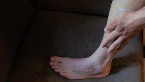 Een jonge mens maakt een strook voor ontharing op zijn been vast de kerel zette zijn voet op het bed, in de was zet benen 4K 4K v stock footage