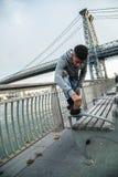 Een jonge mens maakt zijn Timberlands voor Williamsburg B schoon Royalty-vrije Stock Foto's