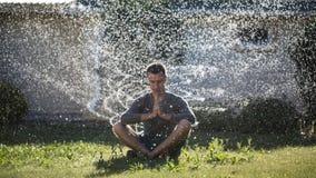 Een jonge mens mediteert onder de nevel van water royalty-vrije stock afbeelding