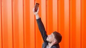 Een jonge mens met een baard klopt zijn hand op de telefoon, vangt de telefoon niet het netwerk, slechte mobiele communicatiemidd stock footage