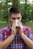 Een jonge mens met een allergie die in zakdoek niezen Royalty-vrije Stock Foto's