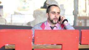 Een jonge mens met een baard die op een celtelefoon spreken stock videobeelden