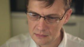 Een jonge mens met glazen, die een computer met behulp van, kijkt, bestudeert Close-up stock footage