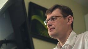 Een jonge mens met glazen, die een computer met behulp van, kijkt, bestudeert Close-up stock video