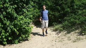 Een jonge mens met een handicap reist de wereld Uit het hout op het strand met een in hand kaart en een rugzak stock videobeelden