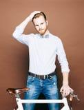 Een jonge mens met snor en baard is dichtbij modieuze moderne fixgear fiets Vlot haar op het hoofd Jeans en overhemd, de boog Stock Foto