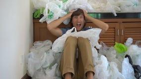 Een jonge mens is omvat met plastic zakken en door de hoeveelheid plastiek met afschuw vervuld die hij gebruikt Het concept van stock footage