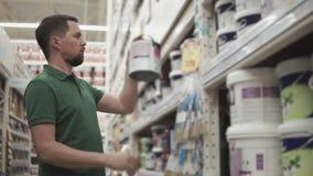 Een jonge mens onderzoekt een blik van verf, leest hij de samenstelling en de kleur stock video