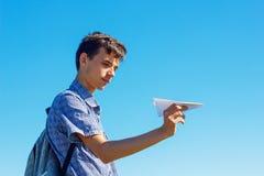 Een jonge mens op een blauwe hemel die een document vliegtuig, het concept vlucht en reis houden royalty-vrije stock fotografie