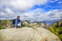 Een jonge mens op de berg het bewonderen mening over Lysefjord noorwegen Royalty-vrije Stock Afbeelding