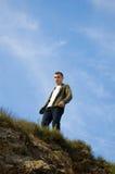 Een jonge mens op de bovenkant van de klip Stock Foto